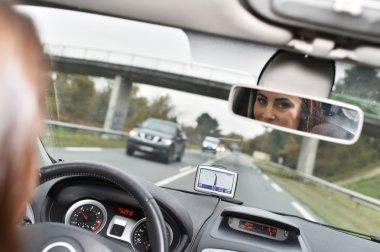 Woman looking at rear view mirror