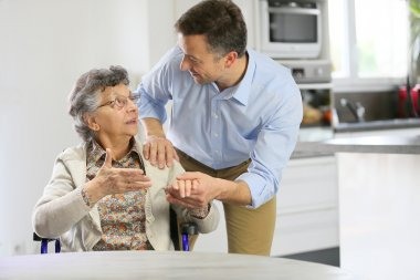Home carer supporting elderly woman