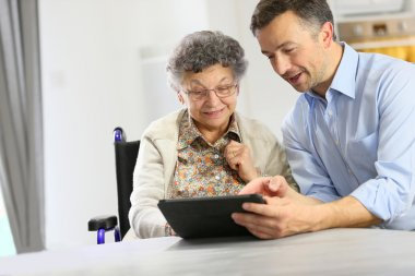 Man with elderly woman using tablet
