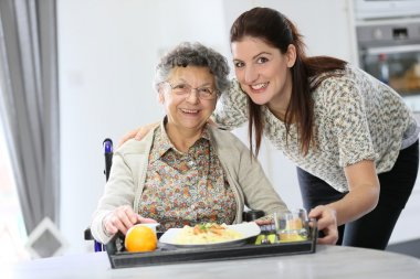 Home carer preparing lunch for woman