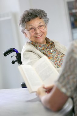 Home carer reading book to woman
