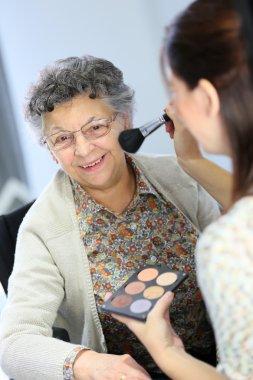 Home carer helping elderly woman