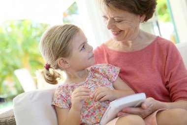 Girl and grandmother with children tablet