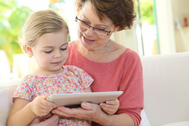 Girl with grandmother playing on tablet