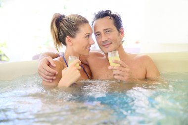 Couple drinking cahmpagne in tub