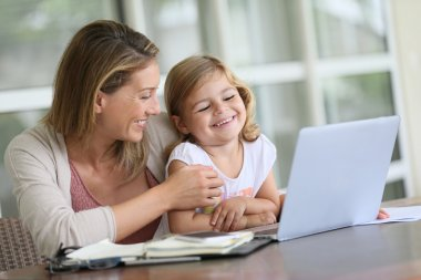 Girl looking at laptop with mother