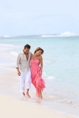 Couple walking on sandy beach