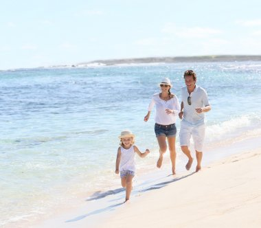 Couple with girl running on beach