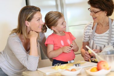Girl with mom and grandmother baking cookies