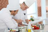 Chef training student in kitchen