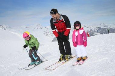 Ski teacher helping kids