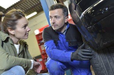 Mechanic showing car wheel