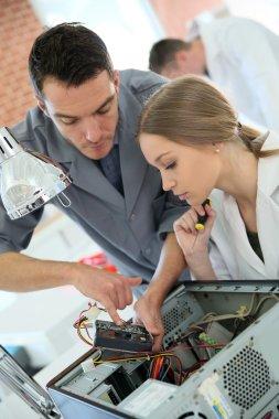 Teacher with student repairing computer