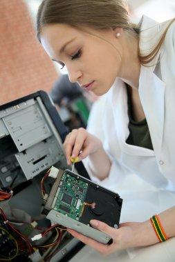 Student girl fixing computer