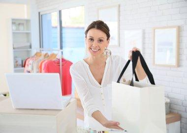 Seller woman giving purchase bag