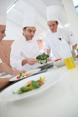 Chef training students in kitchen