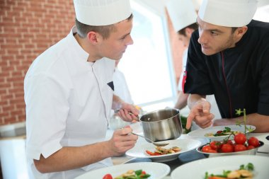 Chef with cook in kitchen