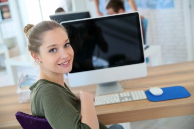 Girl sitting in front of desktop