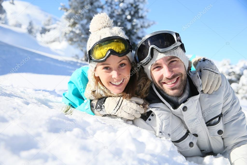 Couple laying down in snow