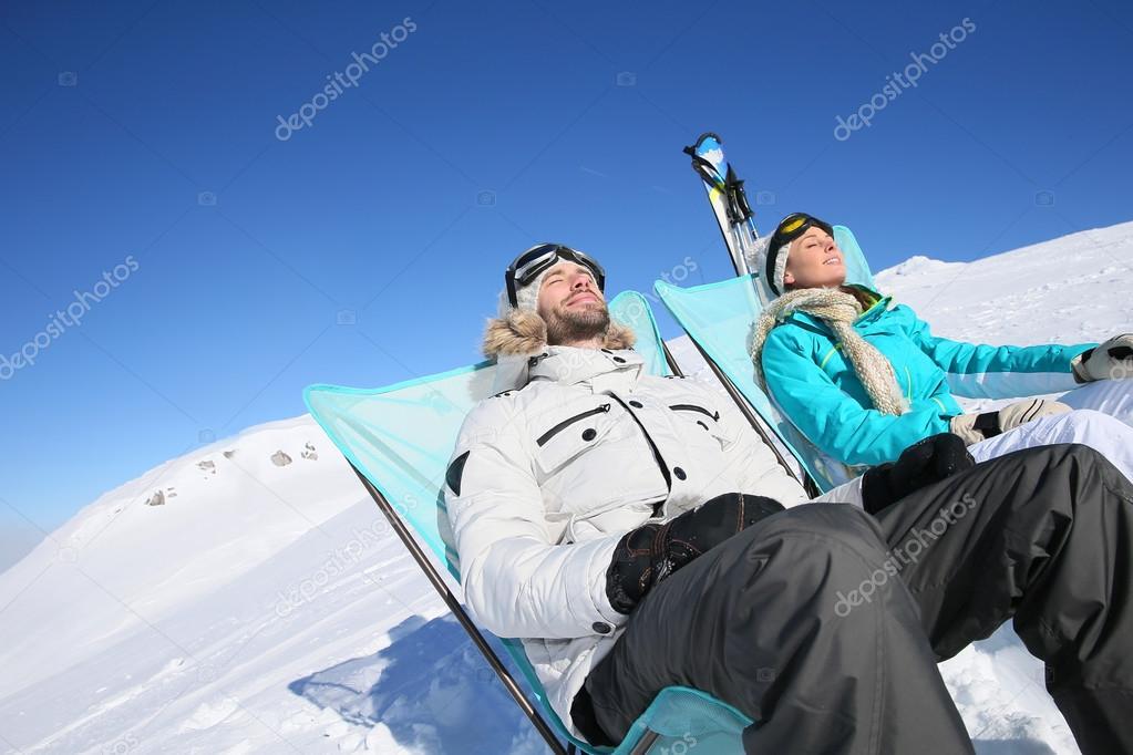 Skiers sunbathing at ski slope