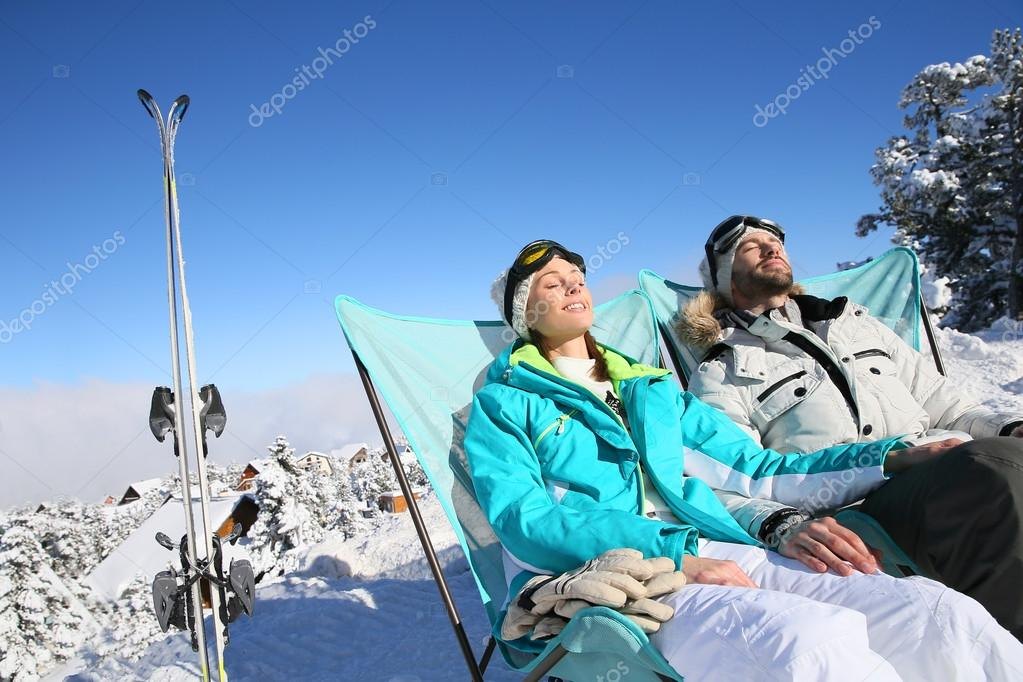 Skiers sunbathing in long chairs