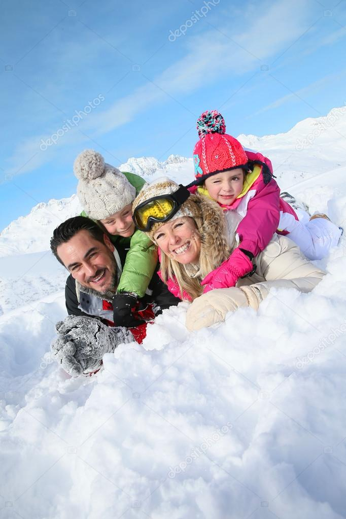 Family laying down in snow