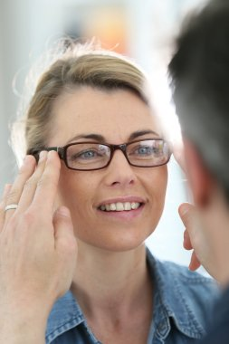 Woman with optician trying eyeglasses