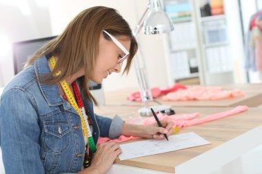 Dressmaker designing clothes pattern