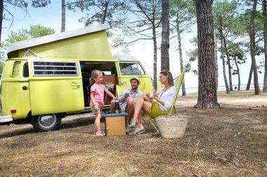 family relaxing by camper van
