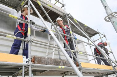 workers installing scaffolding on site