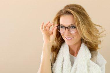 mature woman holding eyeglasses