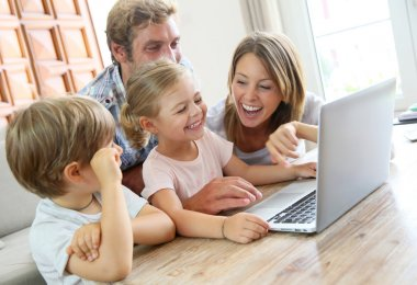 Parents with kids at home using laptop computer