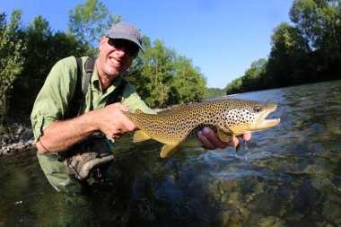 fly-fisherman holding brown truit