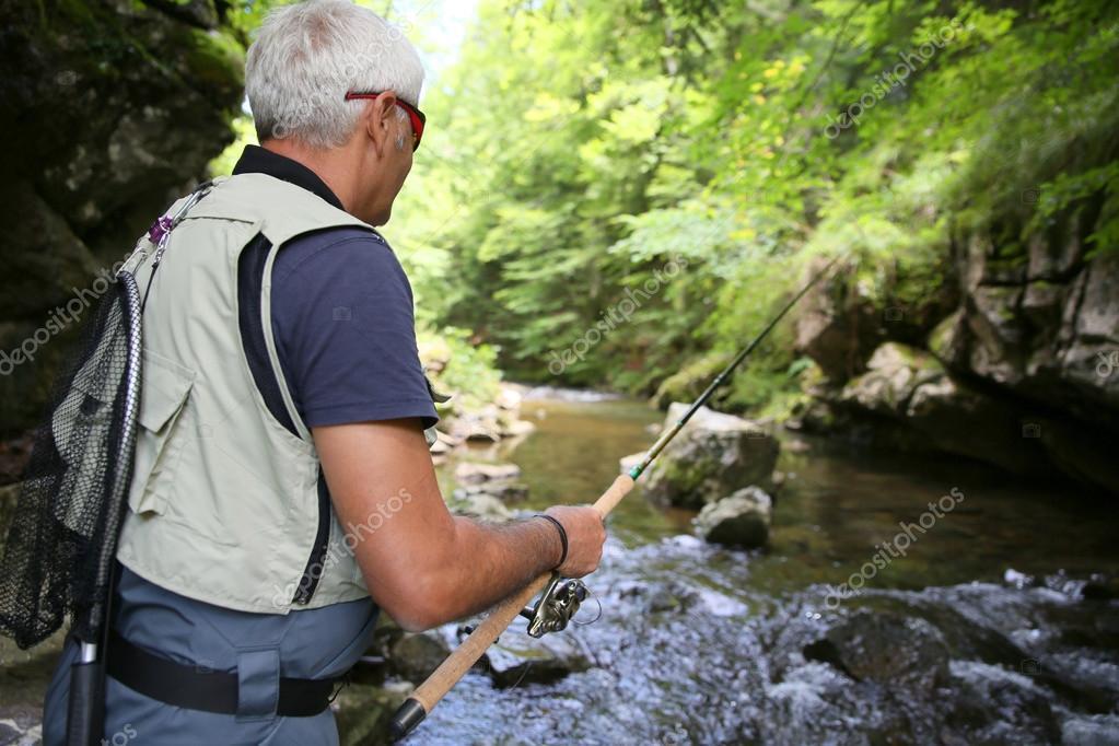 Fly-fisherman fishing in stream