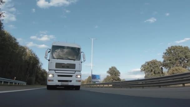 Nákladní vůz s nákladním přívěsem jedoucím po dálnici. White Truck dodává zboží v časných ranních hodinách - velmi nízký úhel jízdy přes zblízka záběr.