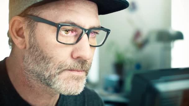 Muž s brýlemi, které pracují na přenosném počítači