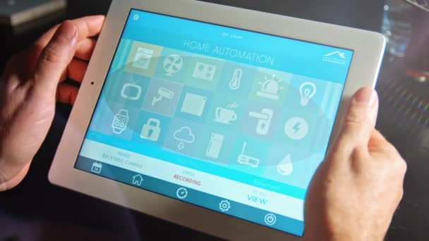 Man uses his tablet PC with smarthome app to control his house