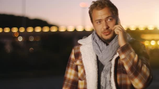 Pohledný mladý muž mluví na smartphone