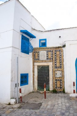 Architectural detail view of traditional Tunisian architecture, whitewashed buildings with ornamental blue doors and windows, North African style streets. stock vector