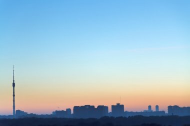 clear blue and yellow daybreak sky over city