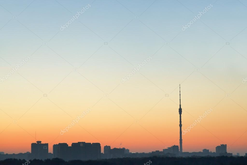 clear blue and yellow sunrise sky over city