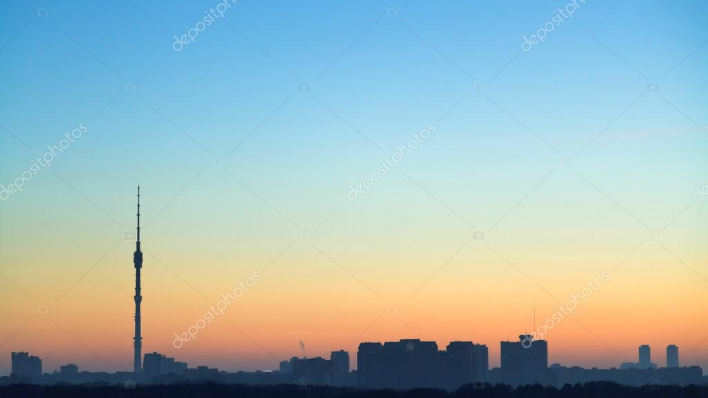 clear blue and yellow dawning sky over city