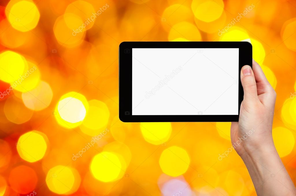 hand with tablet pc on yellow and red background