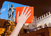 Photo hand deletes Bologna night scene by orange cloth