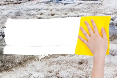 hand deletes melting snow by yellow rag