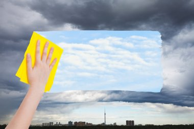 hand deletes rainy cloud over city by yellow cloth