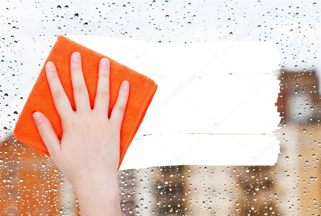 hand deletes rain drops on window by orange rag