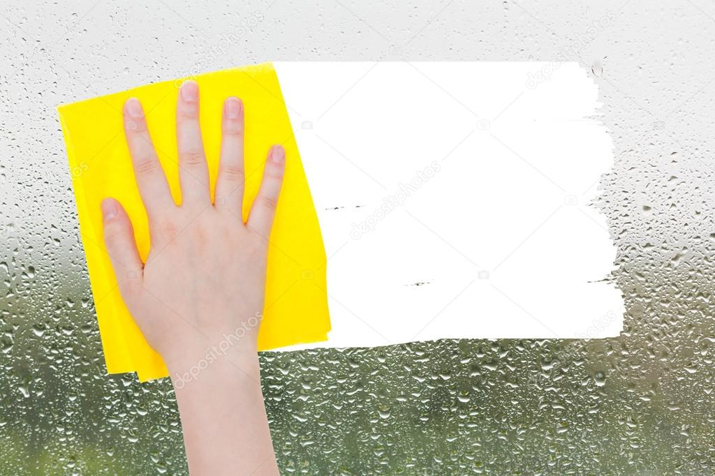 hand deletes raindrops on glass by yellow rag