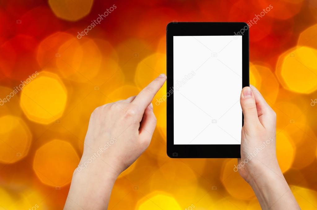 hand with tablet pc on dark red blurred background