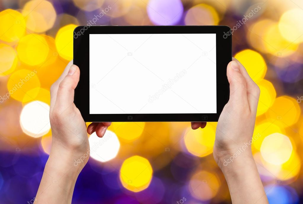 hand with tablet pc on yellow and violet background